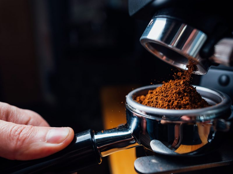 ground coffee pouring into a portafilter with a grinder, closeup